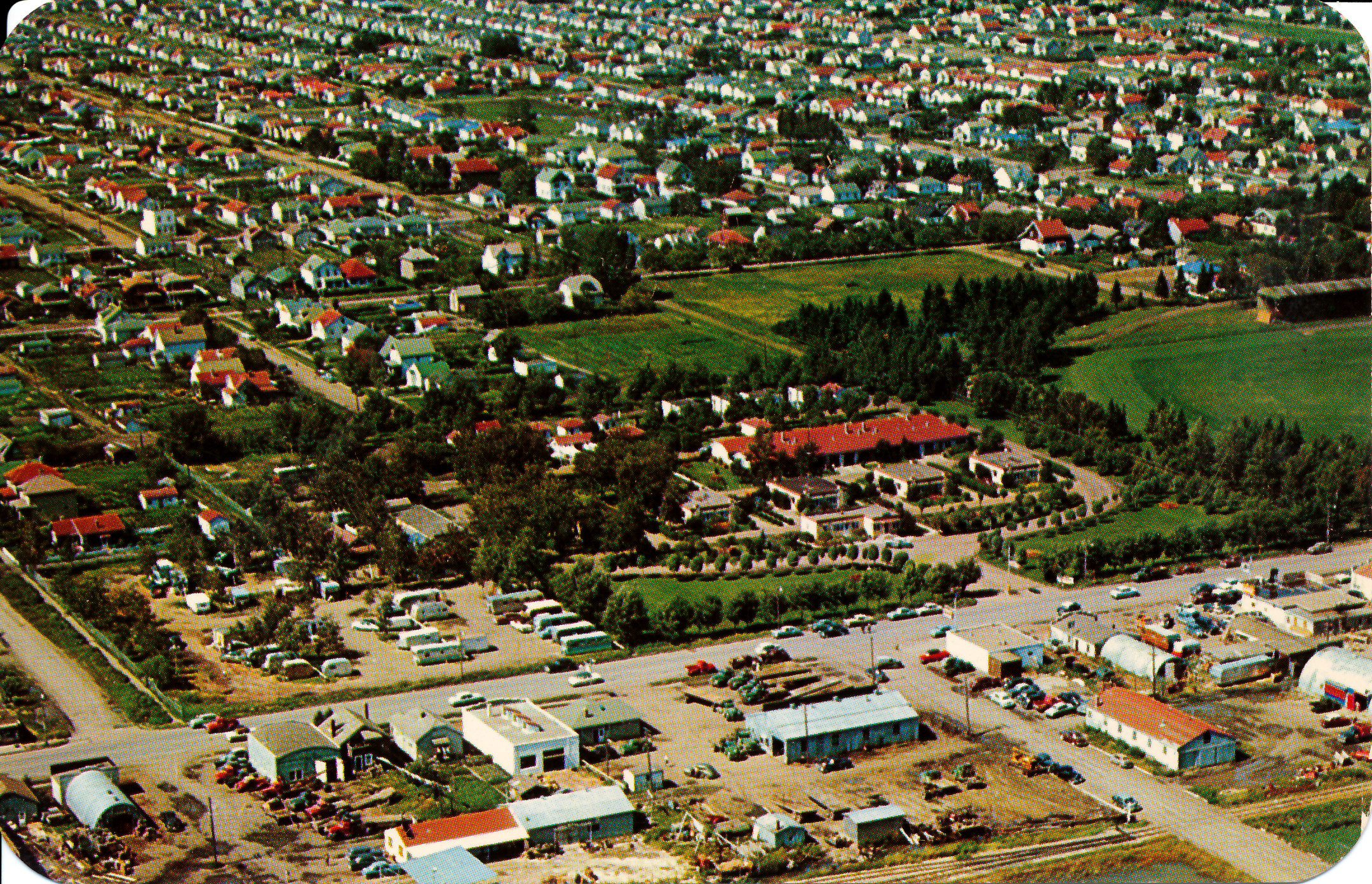 This is an aerial view looking at what was the Edmonton Auto Court. The postcard doesn't specify a year but I can only assume it's sometime before 1953. What we are looking at is 104st southbound going left to right. Where the subject is, the auto court is now where a part of the Scona High School sits. Scona High School was built in 1955 so this was quite some time ago. The little road on the left hand side is 70th Ave. Many of the houses are still there.